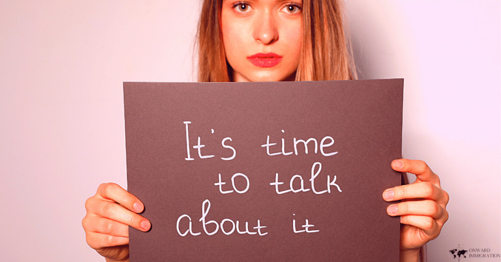 """a woman holding a sign saying """"its time to talk about it"""""""